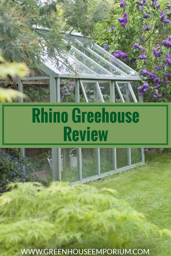 Greenhouse with white frame in a garden and the text: Rhina Greenhouse Review