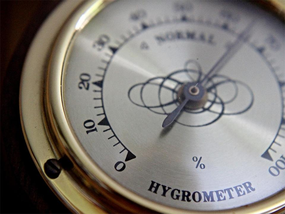 An analog hygrometer with a golden color