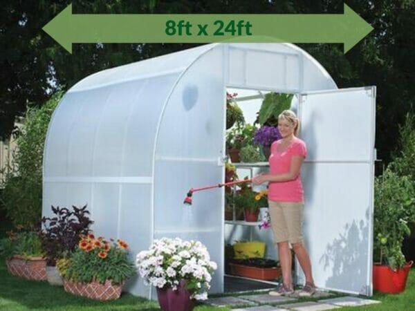 Solexx  8ft x 24ft Gardener's Oasis Greenhouse G-224 - open door - with plants inside - green arrow on top showing dimensions - a woman by the door watering the plants