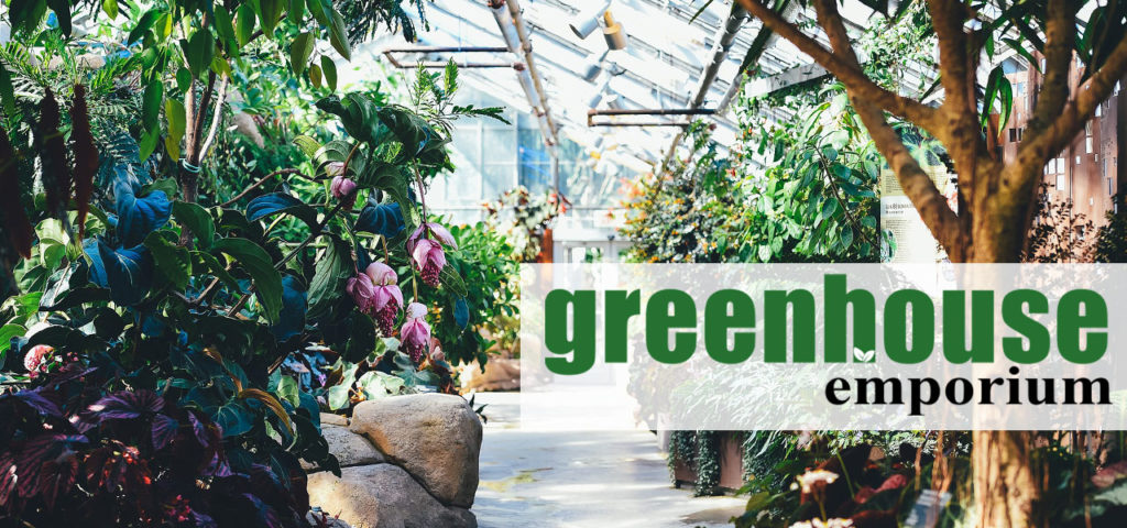 Interior of a huge greenhouse with lots of plants and the Greenhouse Emporium Logo