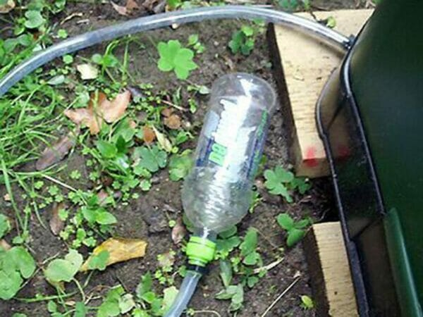 Aerobin 400 Insulated Composter with a pipe attached to a bottle