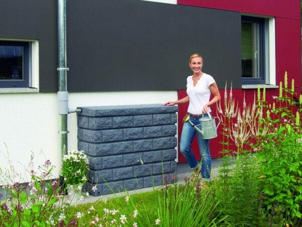 Brick Wall Rain Barrel outdoor set up with a woman carrying a sprinkler stands on the right side of the barrel.