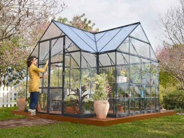 Palram Chalet 12ft x 10ft Hobby Greenhouse HG5400 - in a garden - a woman outside opening the door
