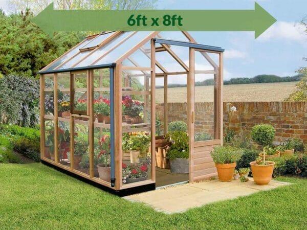 Juliana Classic Greenhouse 6ft x 8ft - open door_green arrow on top showing dimensions - in a garden