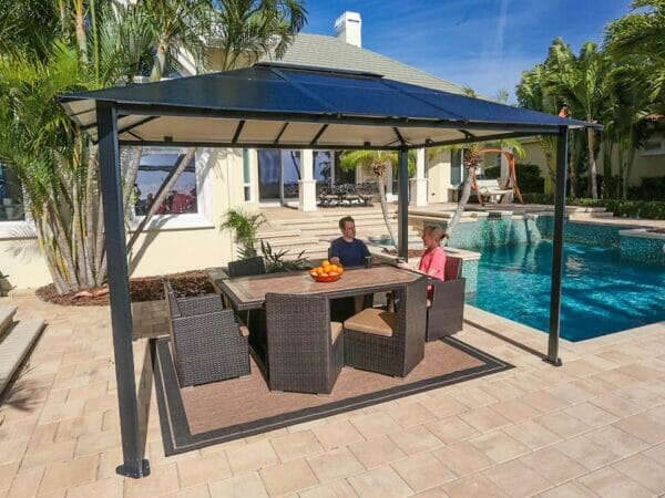 Durham 10x13 Hard Top Gazebo with a dining area set beside the pool