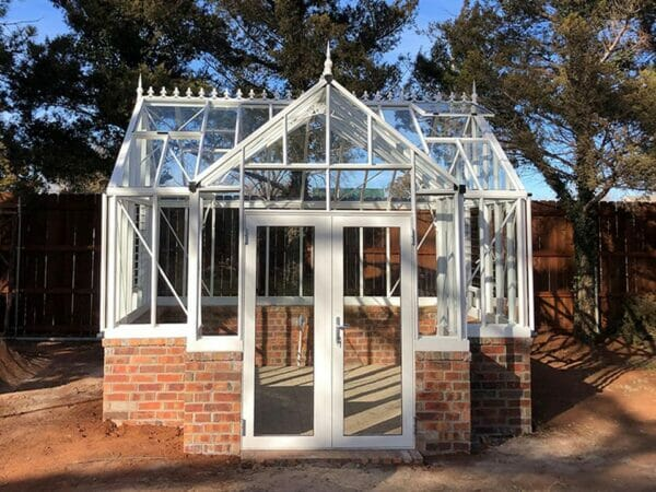 EOS Royal Victorian Antique Orangerie, white frame, freshly constructed on brick stem wall shown with one roof window open, door closed