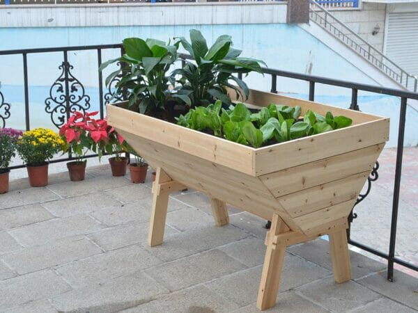 Eden V-Shaped Solid Wood Garden Table with plants on a patio