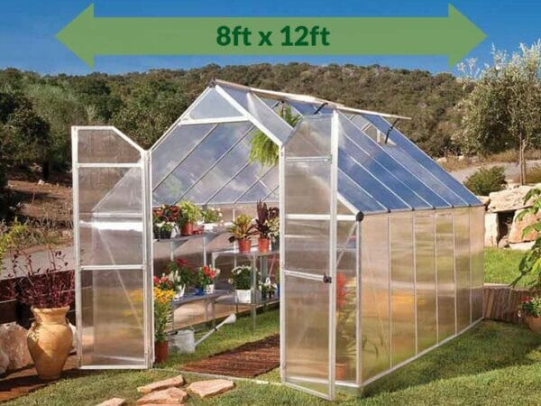Palram Essence 8ft x 12ft Hobby Greenhouse - HG5812 - full view - with green arrow on top - in a garden