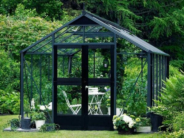 Juliana Premium Greenhouse 9ft x 14ft Anthracite 3mm safety glass with plants inside. Outdoor setting. Front View. Door Closed