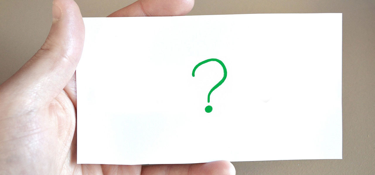 Hand holding a white piece of paper with a green question mark