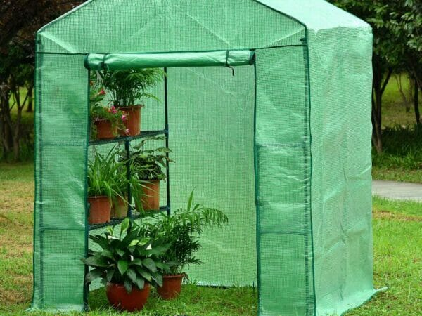 Large green Genesis Portable Walk In Greenhouse with open roll-up door in a garden