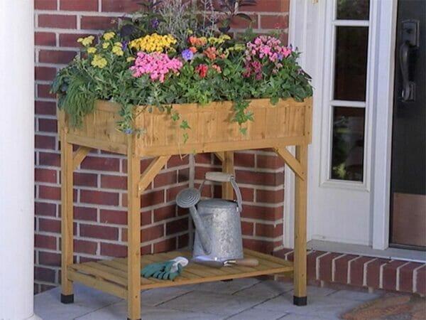 VegTrug Herb Garden Planter with plants and a sprinkler below