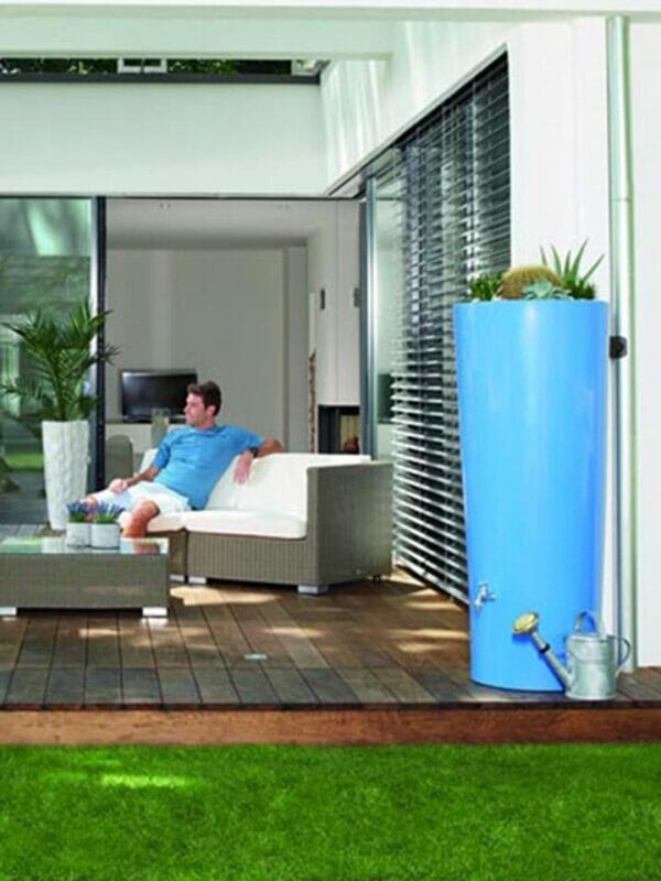 Blue High Gloss Rain Barrel & Planter Outdoor with a sprinkler placed on next to it.