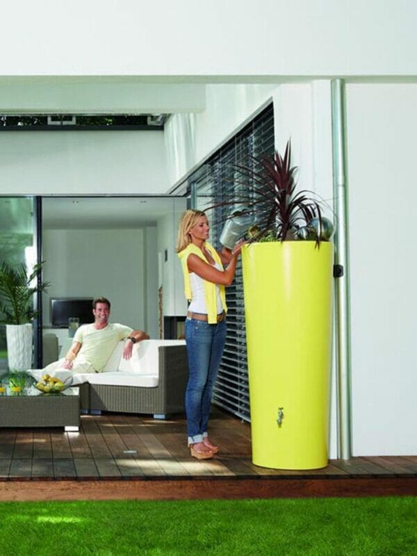 Lemon Yellow High Gloss Rain Barrel & Planter. A woman on the left side watering the plants on top of the barrel.