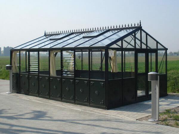 Black frame Retro Victorian VI46 greenhouse on concrete pad, field in background