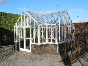 Janssens T-Shaped Royal Victorian Antique Orangerie, white frame with decorative roof ridge, on brick stem wall, in outdoor setting