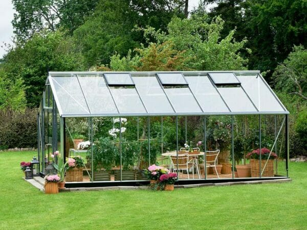 Juliana Gardener Greenhouse 12ft x 19ft - 3mm toughened glass - side view - in a garden