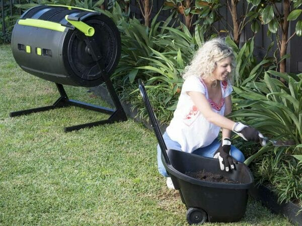 A woman putting mature compost from MAZE Cart in the garden bed while the MAZE composter stands in the background