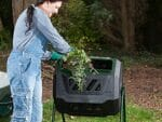 Woman puts organic waste into the Mr. Spin Dual Compartment Compost Tumbler