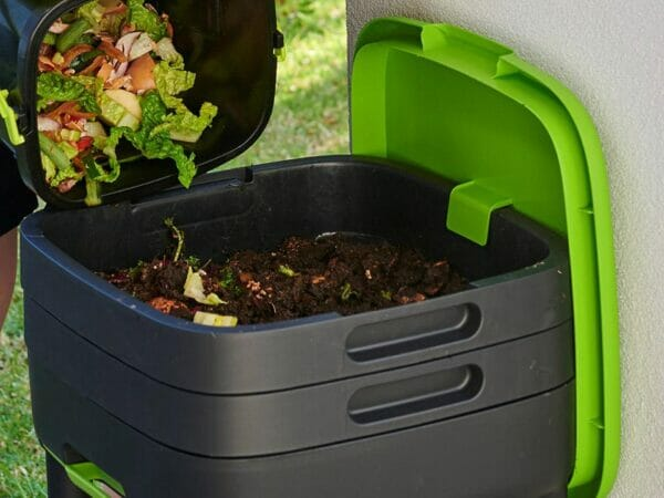 MAZE Worm Farm with open lid at the top and person pouring kitchen scraps into tray
