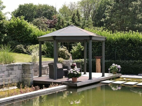 Roma Garden Gazebo in a garden by the pond with a living room set up