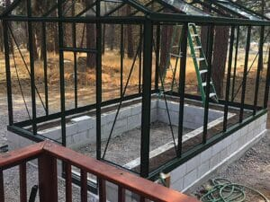 Janssens Royal Victorian Drop-Door Kit installed on a Royal Victorian Greenhouse, which is sitting on a stem wall