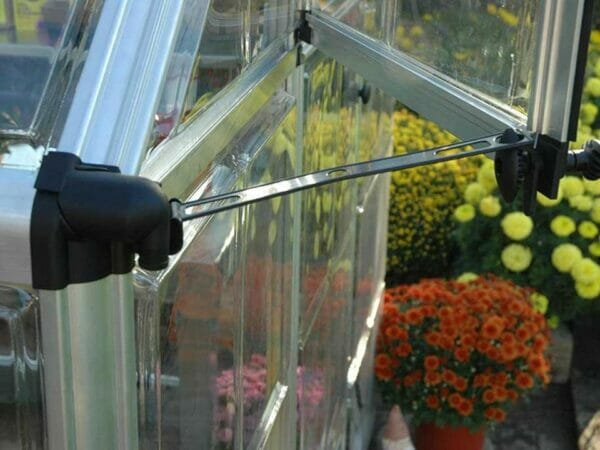 Close up of the Palram 6ft x 16ft Snap & Grow Hobby Greenhouse with flowers for Palram Hobby Greenhouses