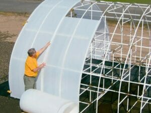 A man installing Solexx Greenhouse Covering Rolls to a greenhouse