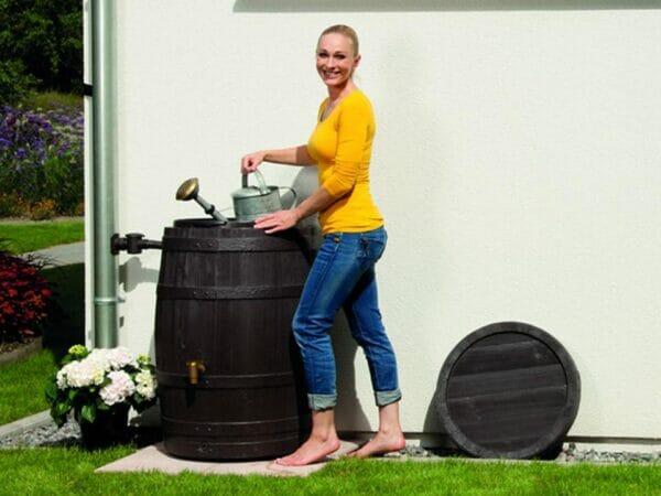 A woman on the left side of VINO Rain Barrel holding a sprinkler