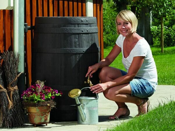 A woman on the right side pouring water from VINO Rain Barrel