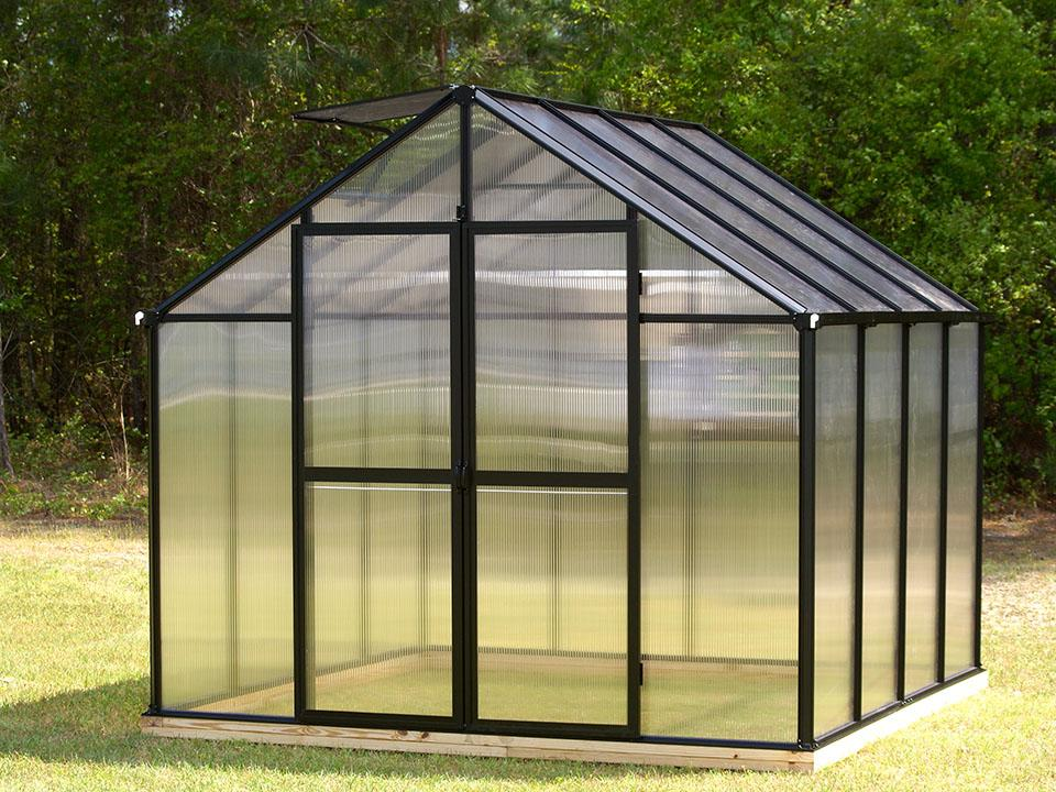 Black-framed Polycarbonate greenhouse in a garden - Monticello Greenhouse Kit