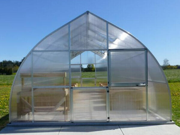 One of the Riga XL Greenhouse line in a garden - gothic-arch shape with two barn-style doors
