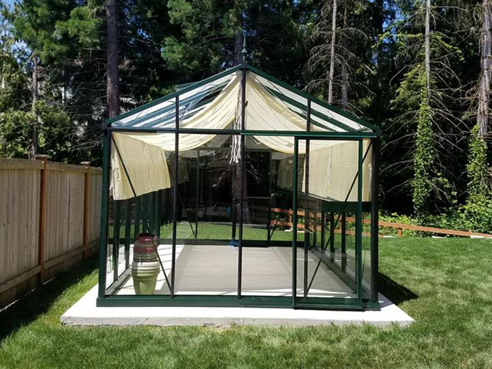 Glass greenhouse on a concrete slab as a greenhouse foundation