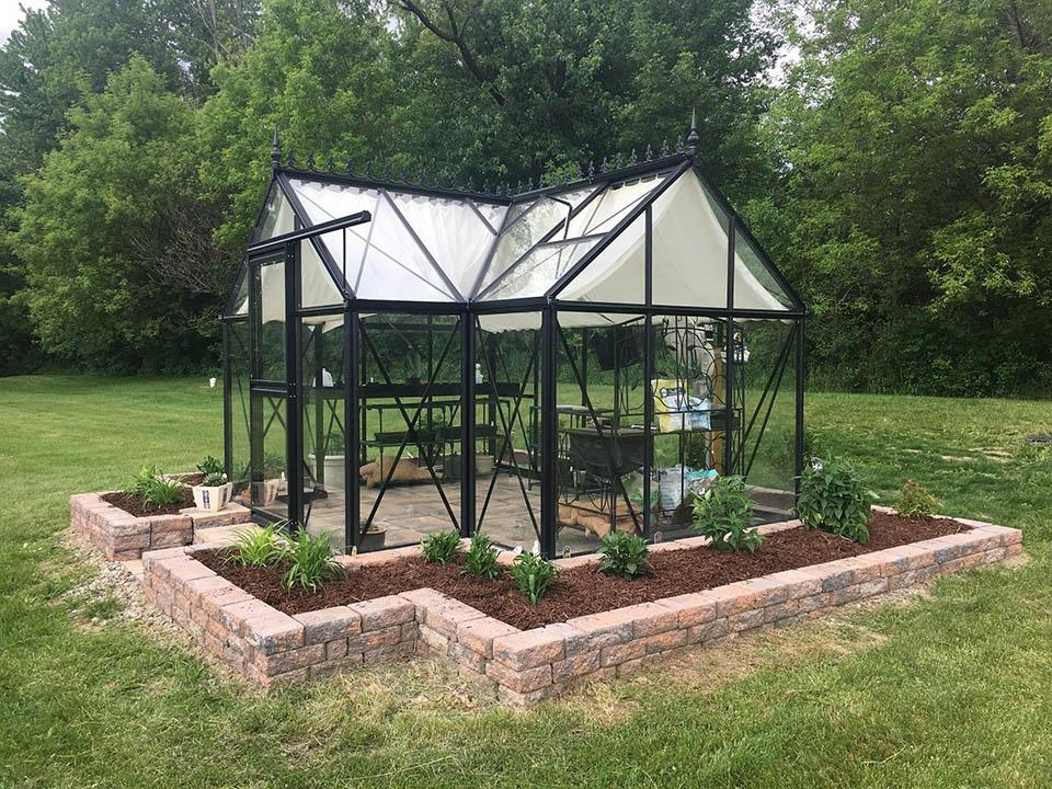 Orangerie greenhouse on a paved foundation with bricks and a framed raised bed surrounding the greenhouse