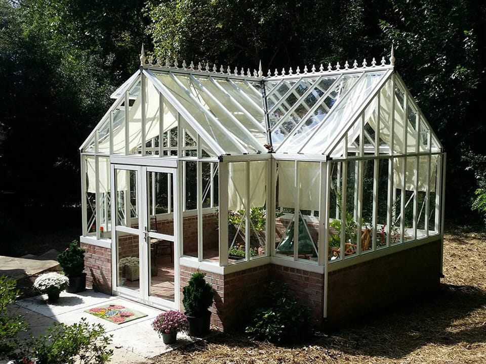 White orangerie greenhouse on a stem wall built with bricks