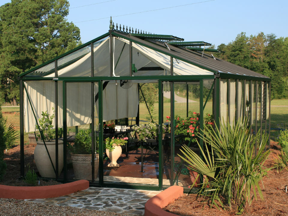 Janssens Royal Victorian greenhouse VI46 exterior view of decorative roof ridge, shade cloths, open sliding door, and open roof windows