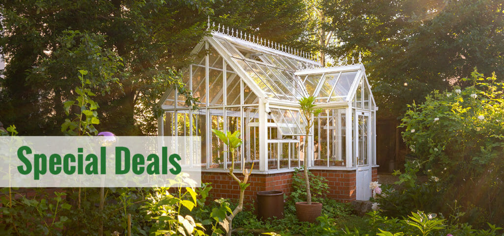 Glass greenhouse with a white frame in a garden and the text: Special Deals
