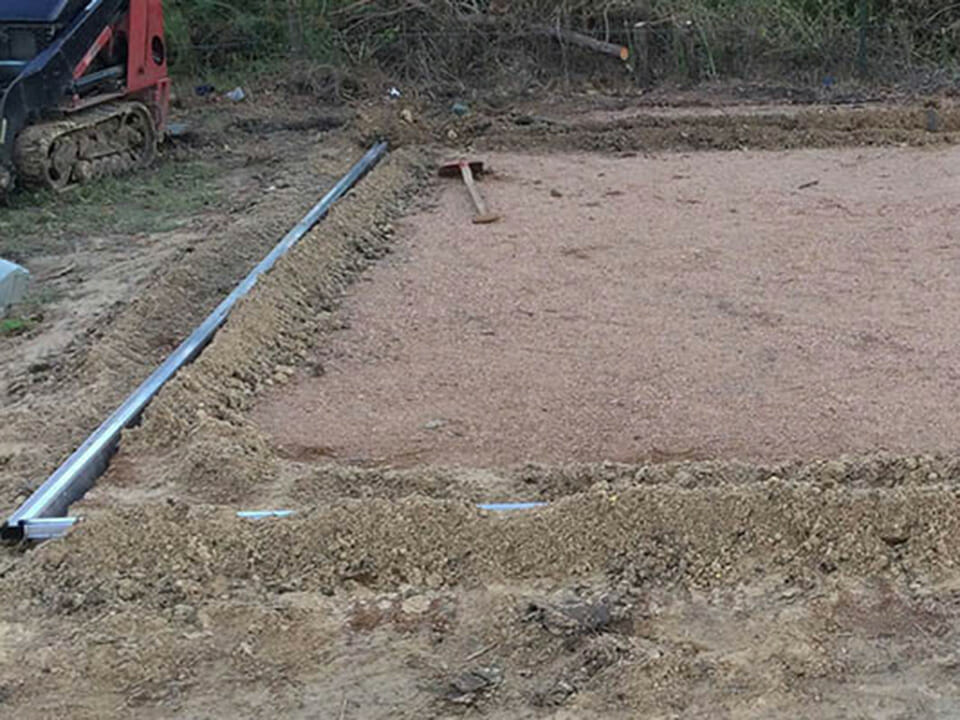 Greenhouse base frame buried in compacted soil as a greenhouse foundation