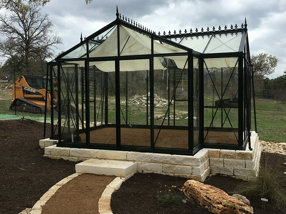 Glass greenhouse on a foundation made of bricks and soil flooring