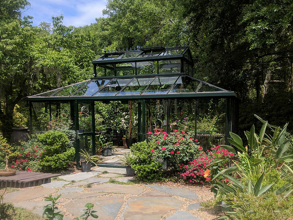 Garden setting with a large glass greenhouse with plants and trees growing inside