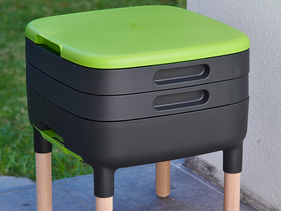 MAZE Worm Farme with black trays and a green lid on wooden legs