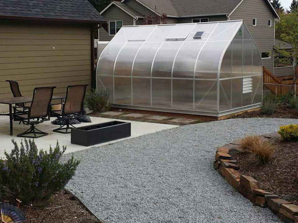 Climapod greenhouse in the backyard next to a patio