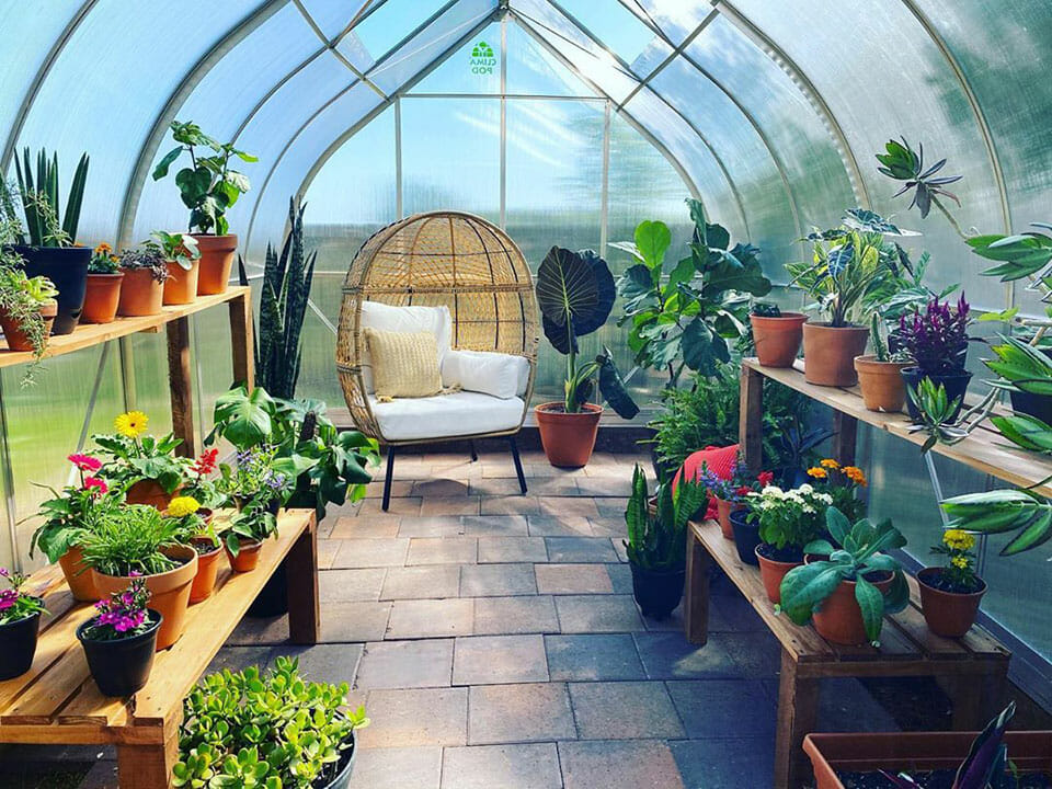 Interior of a Climapod greenhouse with shelves, plants, and a chair