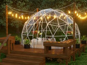 Lumen & Forge 13ft Geodesic Dome greenhouse with white steel frame and clear vinyl cover, night scene, on deck with string lights for illumination