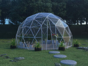 Lumen & Forge 16ft Geodesic dome, clear vinyl cover, on grass lawn with stone stepping stones leading to open zippered door