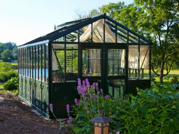 Retro Victorian VI36 greenhouse, green frame with decorative panels, double doors installed at end, shade curtains on interior