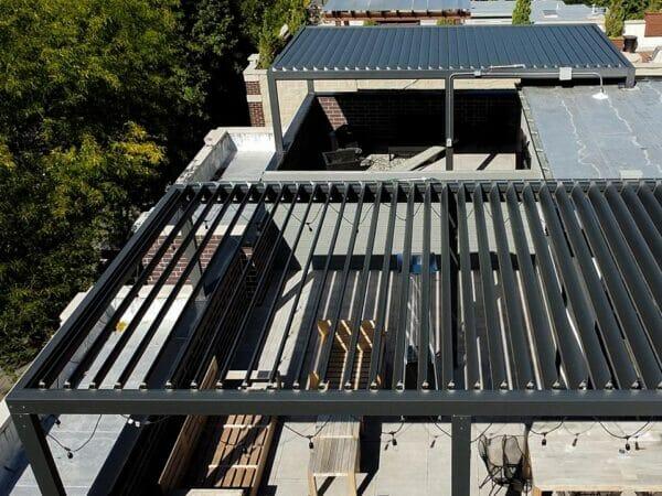 Aerial view of rooftop Selt System Sunbreaker 400 Pergola installation, black, slats open