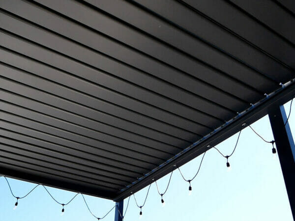 View of Selt System Sunbreaker 400 Pergola roof from underneath structure, black, slats closed, shown with string lights