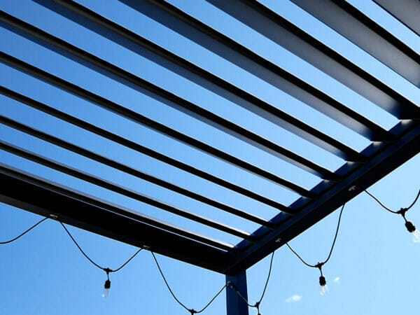View of Selt System Sunbreaker 400 Pergola roof from underneath structure, black, slats open, shown with string lighting installed