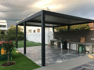 Black pergola, side view, over stone patio with workbench area, slats in closed position